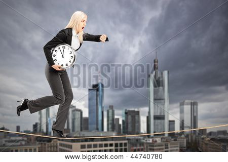 Full length portrait of a businesswoman running on a rope in the business center of Frankfurt, Germany