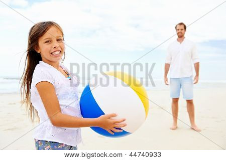 Father and daughter playing on the beach together having fun with beachball