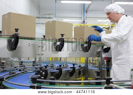 caucasian man worker in white apron, cap and blue gloves at  packing line in factory