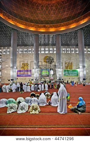 JAKARTA, INDONESIA - DECEMBER 27: Muslim praying at Istiqlal Mesjid Mosque on December 27, 2011 in Jakarta. Tiles pattern on the floor draws the places where worshipers put their prayer carpet.