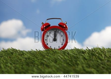 Red alarm clock with two bells on green field