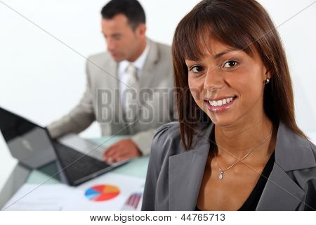 Smiling businesswoman standing in front of a colleague and his laptop