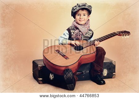 Portrait of a romantic little boy sitting with his guitar. Retro style.