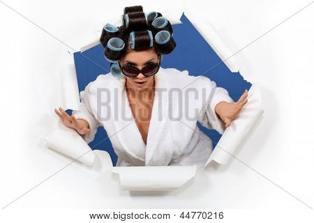 Woman in a bathrobe with her hair in rollers