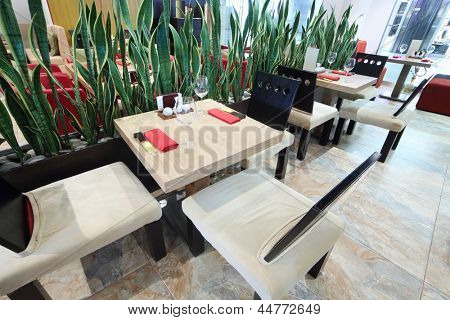 Tables and chairs near green leaves in small Japanese restaurant.
