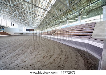 Small covered stadium with long benches and sand coated for horse racing. poster