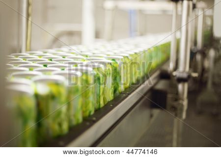 Empty aluminum cans for drinks move on conveyor at large factory. Shallow depth of field.