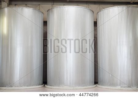Three large clean metal cisterns for liquids in big factory.