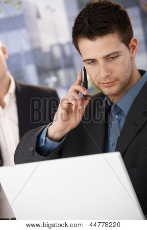 Businessman on mobile phone call holding laptop computer outside of office.