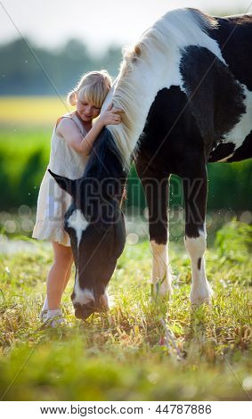 Child stands with a horse in the field.