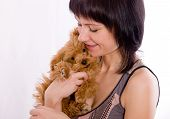 Puppy in embraces of the smiling young woman poster