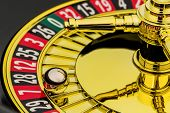 the cylinder of a roulette gambling in a casino. profit and loss is decided by chance. poster