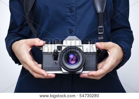 Woman holding a camera over gray background