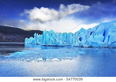 Chilean Patagonia. National Park Torres del Paine. Lake and Glacier Grey. A sharp wind and the cold sun over blue ice. Grey glacier moves down the water of the lake