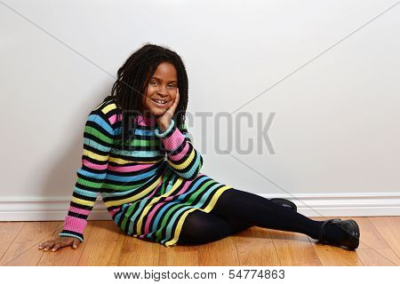 child in colorful dress sitting