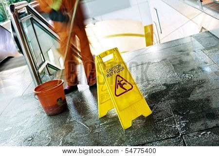 cleaning in progress, and wet floor caution sign besides.