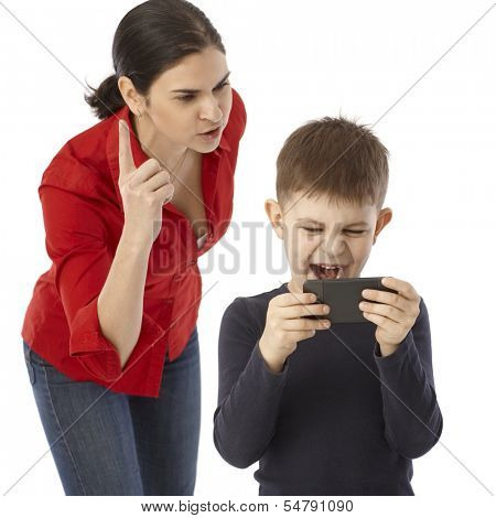 Little boy playing on mother's mobilephone, mother rebuking him.