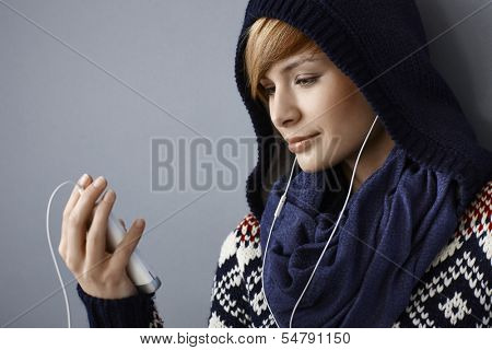 Young woman in hood talking on phone using earbuds