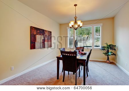 Simple and bright dining room with served table. Decorated with wall picture and fake palm tree