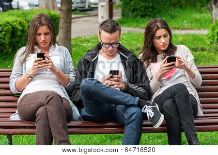 Focused group of friends looking on their phones and not socializing
