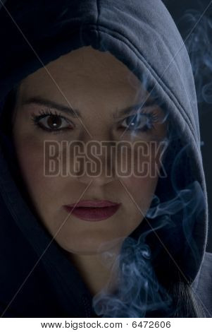 Woman  With Hood And Smoke In Darkness
