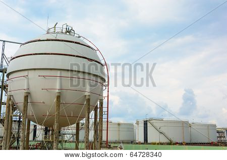 Natural Gas Tank and row of large white tanks for petrol and oil