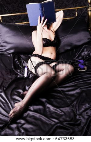 Attractive woman reading an erotic novel in a bed. poster