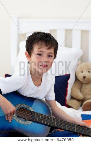 Portrait Of A Little Boy Playing Guitar