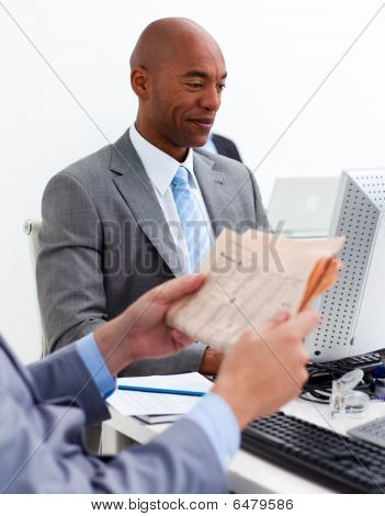 Smiling Businessman Working At A Computer With His Colleague Reading A Newspaper