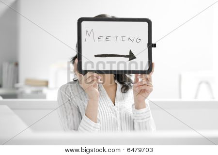 Young Woman Holding 'meeting' Sign