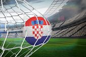 Football in croatia colours at back of net against large football stadium with lights poster