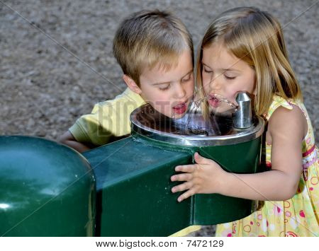 Kids drinking water from a public fountain poster