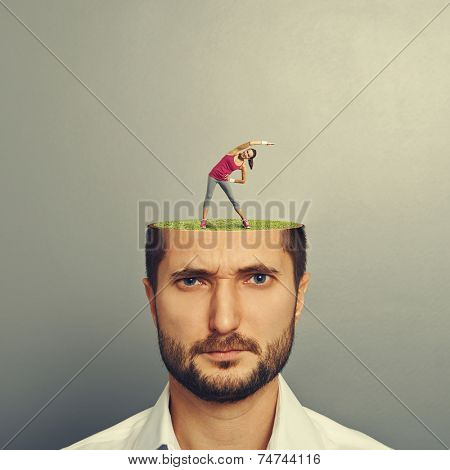 portrait of displeased man with cut head. small pretty woman doing fitness exercises on the green meadow in mans head. photo over grey background