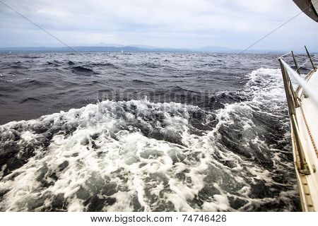 Sea overboard boat in cloudy weather. Sailing regatta in the open sea. Yachting.