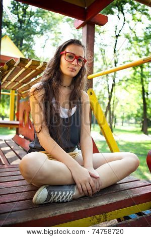 Pretty girl with red glasses sitting on climbing frame in park