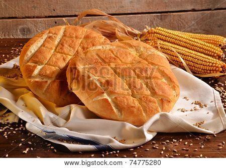 Foccacia Italian bread on rustic wood table and ingredients.Rustic bread and corn on an old vintage wood table.