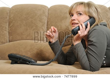 The Woman Speaking By Phone On A Sofa