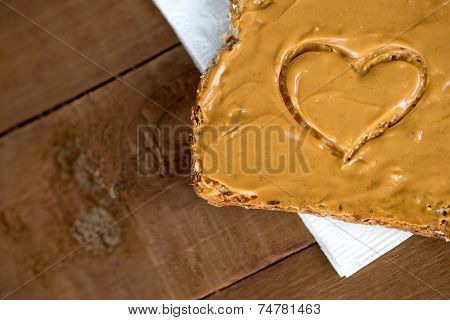 Closeup Of Peanut Butter Toast With Heart Shape On Tissue Against Wood