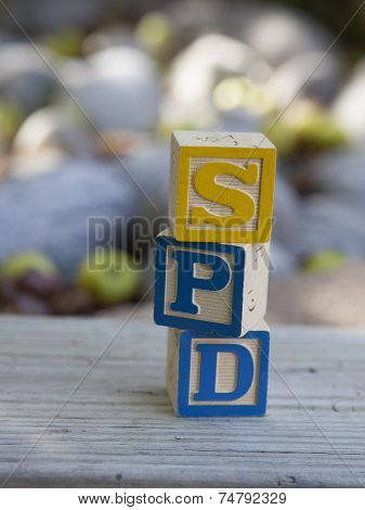Alphabet blocks arranged to spell SPD - Sensory Processing Disorder poster