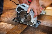 Detail of carpenters hand grinding wooden planks poster