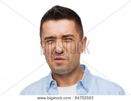 emotions, facial expression and people concept - man wrying of unpleasant smell