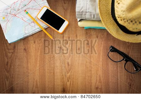 travel, summer vacation, tourism and objects concept - close up of folded clothes, smartphone and touristic map on wooden table