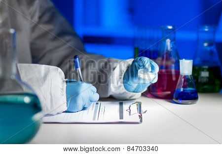 science, chemistry, medicine and people concept - close up of young scientist with chemical sample taking notes on clipboard and making test or research in laboratory