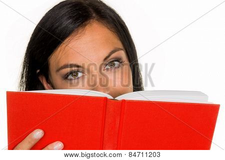 a young woman reading a book with a red cover