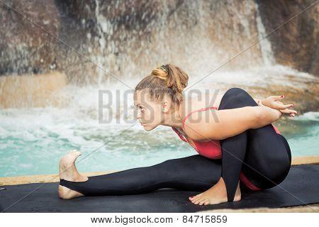 Woman practicing yoga near waterfall. Sage pose. Marichyasana