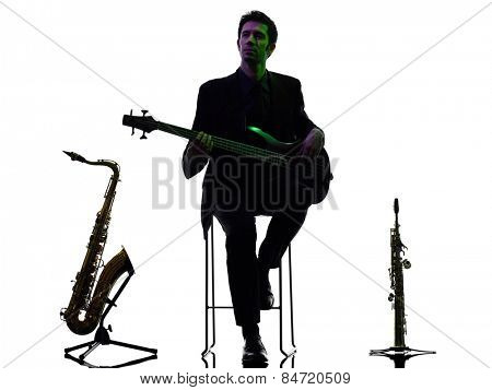 one caucasian man guitarist bassist player playing in studio silhouette isolated on white background