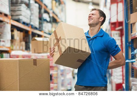 Side view of worker with backache while lifting box in the warehouse