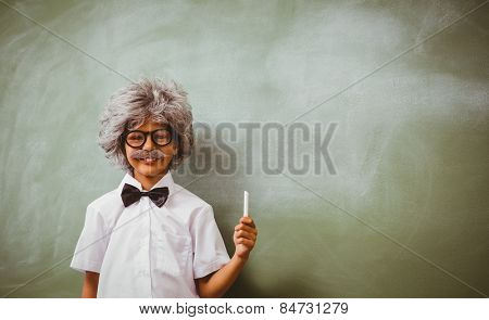Portrait of little boy dressed as senior teacher in front of blackboard