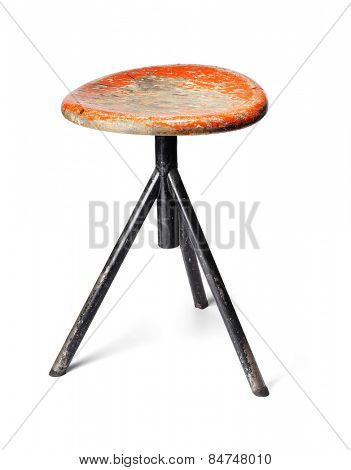 Old thee-legged stool from a workshop. Isolated on white with natural shadows.