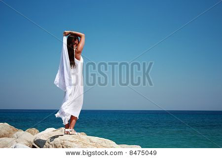 Woman standing on a cliff in a long white dress